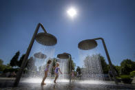 Children cool off in a public fountain in Vilnius, Lithuania, Saturday, June 19, 2021. The heat wave continues in Lithuania as temperature rose to as high as 32 degrees Celsius (89.6 degrees Fahrenheit). (AP Photo/Mindaugas Kulbis)