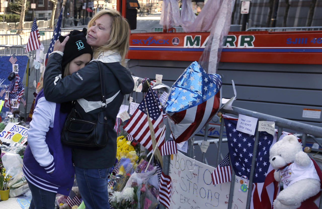 Holly Holland, right, of St. Louis, hugs her daughter Katie Holland while visiting a makeshift memorial in Boston, Monday, April 22, 2013. The memorial sits on Boylston Street, not far from where two bombs exploded near the finish line of the Boston Marathon, on Monday, April 15. (AP Photo/Steven Senne)