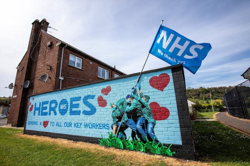 Street art graffiti paying tribute to the NHS, (National Health Service), is pictured on a wall in Glynn, north of Belfast on May 5, 2020. - The number of people killed by the coronavirus in the UK stands at 32,313, according to official figures on May 5 2020, the second highest death toll in the world. Figures from the Office for National Statistics showed Britain had now overtaken Italy, which has reported 29,029 fatalities, and now only stands behind the US with 68,700 deaths, the largest single-country toll. (Photo by Paul Faith / AFP) (Photo by PAUL FAITH/AFP via Getty Images)