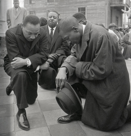 Civil rights leader Martin Luther King Jr. kneels with a group in prayer prior to going to jail in Selma, Alabama. (Getty Images)
