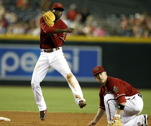 Arizona Diamondbacks shortstop Didi Gregorius, left, turns the double play while avoiding second baseman Aaron Hill, right, in the fourth inning during a baseball game against the Colorado Rockies, Sunday, Aug. 10, 2014, in Phoenix. (AP Photo/Rick Scuteri)
