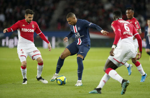 PSG's Kylian Mbappe, center, is challenged by Monaco's Tiemoue Bakayoko, right, and Monaco's Cesc Fabregas, left, during the French League One soccer match between Paris-Saint-Germain and Monaco at the Parc des Princes stadium in Paris, Sunday Jan. 12, 2020. (AP Photo/Francois Mori)