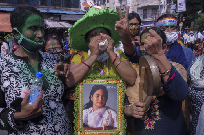Supporters of Trinamool Congress party chief Mamata Banerjee holding an earlier photograph of her celebrate early lead for the party in the West Bengal state elections in Kolkata, India, Sunday, May 2, 2021. (AP Photo/Ashim Paul)