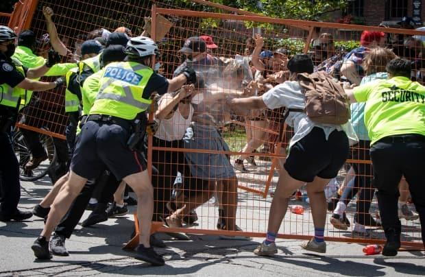 Demonstrators attempting to topple a fence are pepper sprayed by Toronto police officers enforcing an eviction order at an encampment at Lamport Stadium park on July 21, 2021. (Evan Mitsui/CBC - image credit)