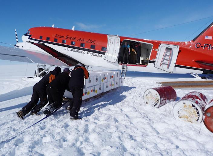 In this Dec. 17, 2012 photo released by scientist Nancy Bertler, scientists and staff push a sled containing crates of ice they've collected in order to load them on a plane on Roosevelt Island, Antarctica. The continent's pristine habitat provides a laboratory for scientists studying the effects of climate change. (AP Photo/Nancy Bertler)
