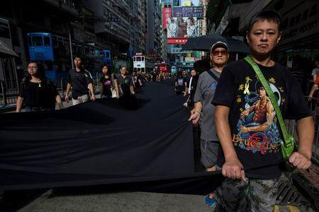 An Occupy Central protester, wearing a t-shirt with an image of martial artist and actor Bruce Lee, marches with fellow demonstrators as they hold a 500-meter long black cloth in Hong Kong, September 14, 2014. REUTERS/Tyrone Siu