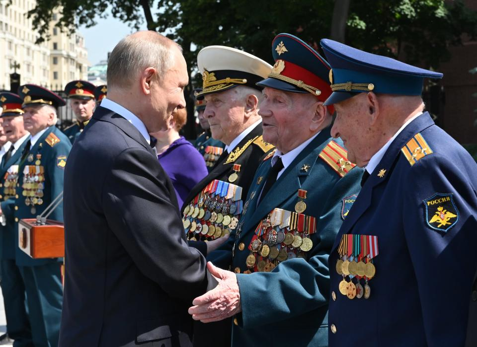 Russian President Vladimir Putin, left, greets Russian WWII veterans during a wreath laying ceremony at the Tomb of Unknown Soldier in Moscow, Russia, Tuesday, June 22, 2021, marking the 80th anniversary of the Nazi invasion of the Soviet Union. (Alexei Nikolsky, Sputnik, Kremlin Pool Photo via AP)