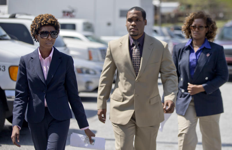 Defendants in Atlanta's school cheating scandal Starlette Mitchell, left, and Angela Williamson, right, turn themselves in at the Fulton County Jail accompanied by attorney Gerald Griggs, Tuesday, April 2, 2013, in Atlanta. Thirty-five defendants are named in a 65-count indictment that alleges a broad conspiracy involving cheating on standardized tests in Atlanta Public Schools. All 35 defendants must turn themselves in Tuesday. (AP Photo/David Goldman)