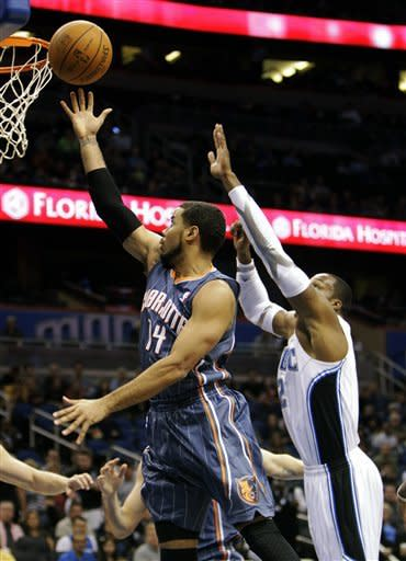 Charlotte Bobcats' D.J. Augustin (14) goes in for a layup past Orlando Magic's Dwight Howard during the first half of an NBA basketball game, Tuesday, Jan. 17, 2012, in Orlando, Fla. (AP Photo/John Raoux)
