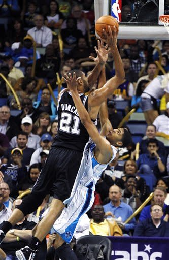 San Antonio Spurs power forward Tim Duncan (21) drives to the basket over New Orleans Hornets power forward Anthony Davis (23) in the first half of an NBA basketball game in New Orleans, Wednesday, Oct. 31, 2012. (AP Photo/Gerald Herbert)