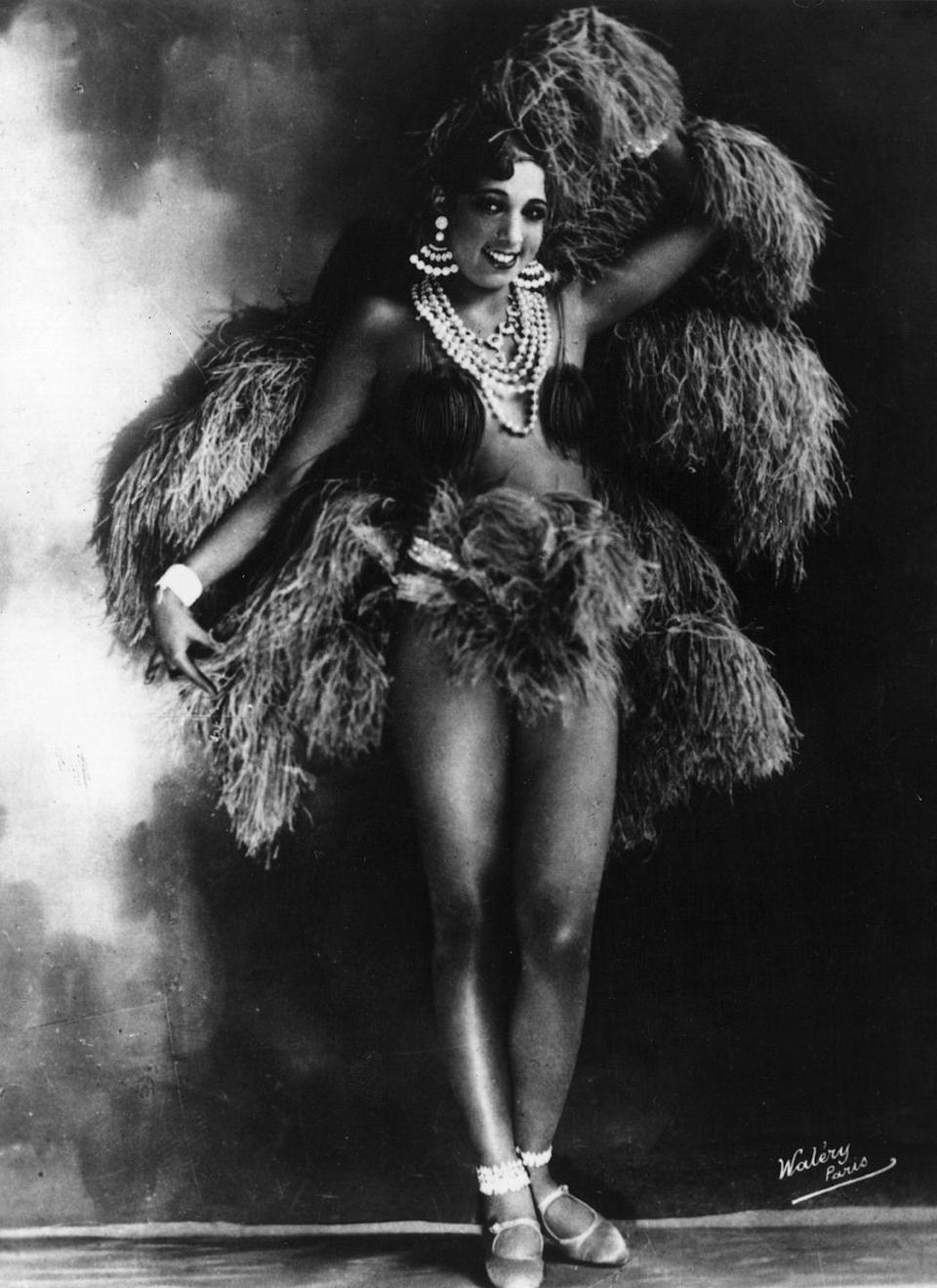 <p>An elaborate costume of feathers, chunky jewelry, and a large headpiece give Baker, who performed with the Parisian Folies Bergere, an otherworldly air.<br></p>
