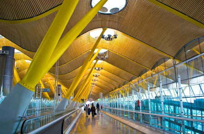 <p><strong>Where: </strong>Madrid, Spain</p>  <p>The design of in the Madrid-Barajas Airport has been described as joyful and exuberant. We'd like to throw in whimsical and inspiring too. The undulating wooden ceiling is supported by a canopy of rainbow colored trees that makes it seem like you're walking through a magical forest. Other notable design elements include the massive, disk-shaped lights and air conditioning vents, which look like sculptures. The architects, the Richard Rogers Partnership (as it was then called), won the prestigious Stirling Design in 2006 for their work on Terminal 4.</p>  <p><strong>Plan Your Trip: </strong>Visit </p>