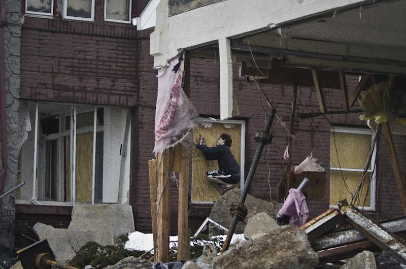 Marcus Konner, 22, boards his home in the aftermath of a storm surge from Hurricane Sandy, Tuesday, Oct. 30, 2012, in Coney Island's Sea Gate community in New York. (AP Photo/Bebeto Matthews)