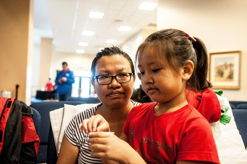 Jie Zhang, 38, and her daughter Sheryl, 8, wait to be entered into the shelter at Lakewood Church in Houston.  (Joseph Rushmore for HuffPost)