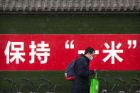 A man wearing a face mask to protect against the spread of the coronavirus walks past a billboard urging people to keep 1 meter apart for social distancing during a snowy morning in Beijing, Tuesday, Jan. 19, 2021. A Chinese province near Beijing grappling with a spike in coronavirus cases is reinstating tight restrictions on weddings, funerals and other family gatherings, threatening violators with criminal charges. (AP Photo/Mark Schiefelbein)