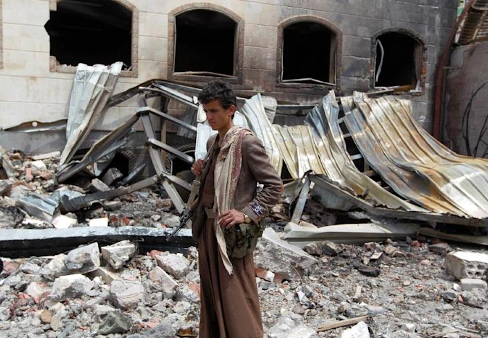 An armed young Yemeni man stands amidst the debris of a house destroyed in an air-strike by the Saudi-led coalition in Sanaa on July 6, 2015 (AFP Photo/Mohammed Huwais)