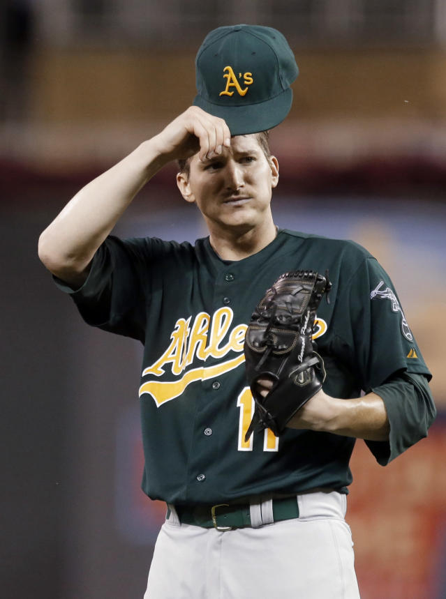 Oakland Athletics pitcher Jarrod Parker takes off his cap after giving up a solo home run to Minnesota Twins' Oswaldo Arcia in the sixth inning of a baseball game, Tuesday, Sept. 10, 2013 in Minneapolis. The Twins won 4-3. Parker, the starter, did not figure in the decision. (AP Photo/Jim Mone)