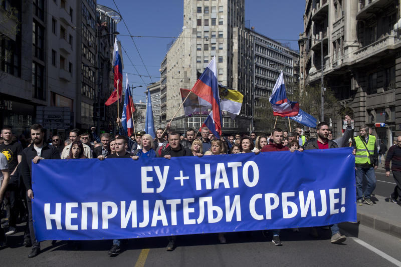 Supporters of the ultranationalist Serbian Radical Party march down a street during a protest in Belgrade, Serbia, Sunday, March 24, 2019. Members of the ultranationalist Serbian Radical Party gathered for a protest on Sunday in the Serbian capital to mark the 20th anniversary of the NATO led bombing campaign against Serbia in 1999. The banner reads 'EU + NATO, Enemies of Serbia!' in Serbian Cyrillic letters. (AP Photo/Marko Drobnjakovic)