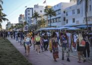 Spring break tourists walk alongside Ocean Drive in Miami Beach, Fla., Sunday night, March 21, 2021. An 8 p.m. curfew has been extended in Miami Beach after law enforcement worked to contain unruly crowds of spring break tourists. (Carl Juste/Miami Herald via AP)