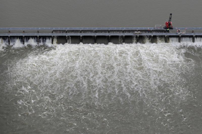 FILE- In this May 10, 2019 file photo, workers open bays of the Bonnet Carre Spillway, to divert rising water from the Mississippi River to Lake Pontchartrain, upriver from New Orleans, in Norco, La. It will be months before state officials know whether losses from floods and spillway openings qualify Louisiana as a fisheries disaster. Department of Wildlife and Fisheries officials say floods began around November 2018, and a full 12 months' data is needed to compare to averages for the previous 5 years. The governors of Louisiana, Mississippi and Alabama asked months ago for US Commerce Secretary Wilbur Ross to declare a fisheries disaster, making federal grants available to affected people. (AP Photo/Gerald Herbert, File)