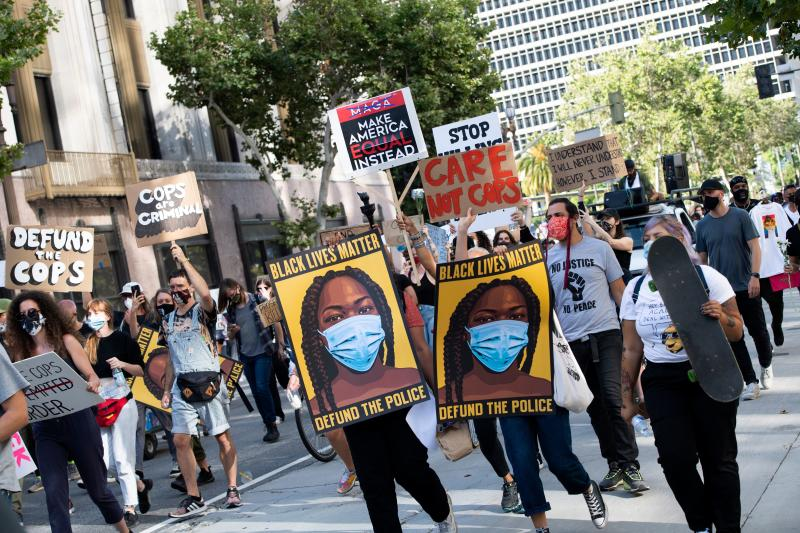 Protesters holding signs march down Spring Street during a demonstration asking for the removal of District Attorney Jackie Lacey, in Los Angeles, California, on June 17, 2020. (Valerie Macon/AFP via Getty Images)