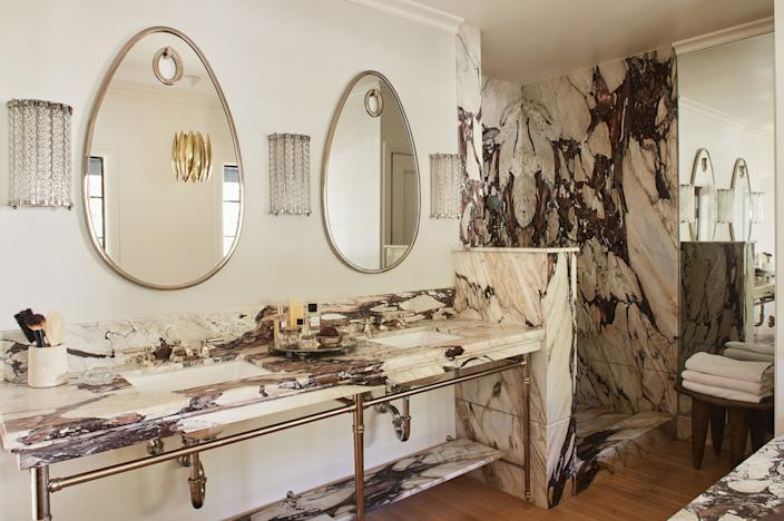 "<div class=""caption""> ""I wanted something very dramatic,"" Dahan says of the maroon veins in her Calacatta Viola marble master bath. Two Hubert Le Gall mirrors hover over each sink, and vintage brass lighting sets the mood. </div>"