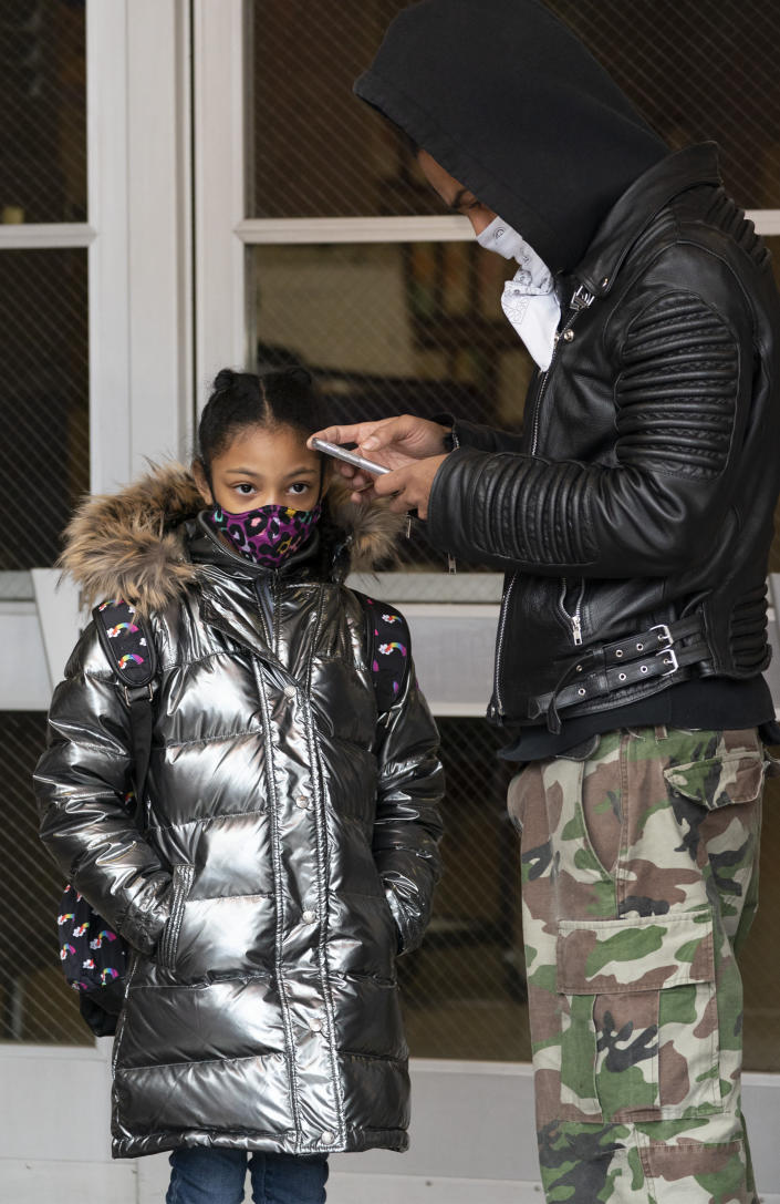 Dante Kneece and his step-daughter Marciella wait for P.S. 134 Henrietta Szold Elementary School to open, Monday, Dec. 7, 2020, in New York. Public schools reopened for in-school learning Monday after being closed since mid-November. (AP Photo/Mark Lennihan)