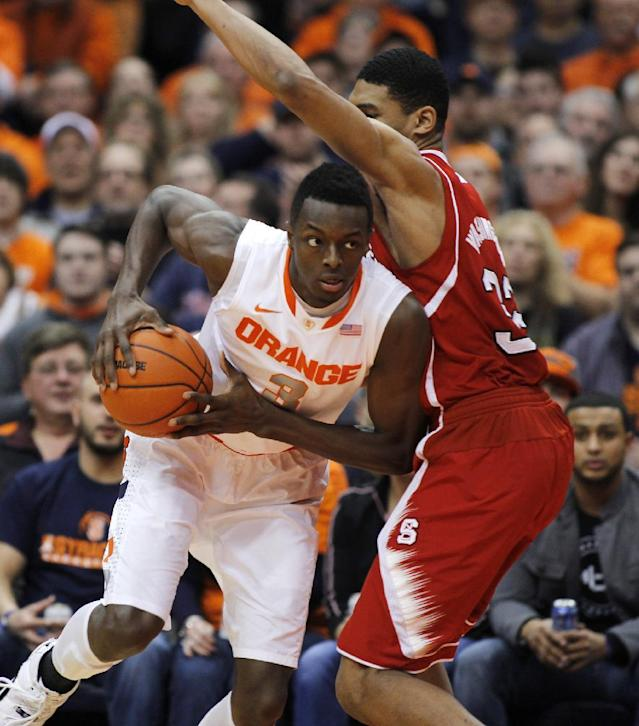 Syracuse's Jerami Grant, left, dives around North Carolina State's Kyle Washington, right, during the first half of an NCAA college basketball game in Syracuse, N.Y., Saturday, Feb. 15, 2014. (AP Photo/Nick Lisi)