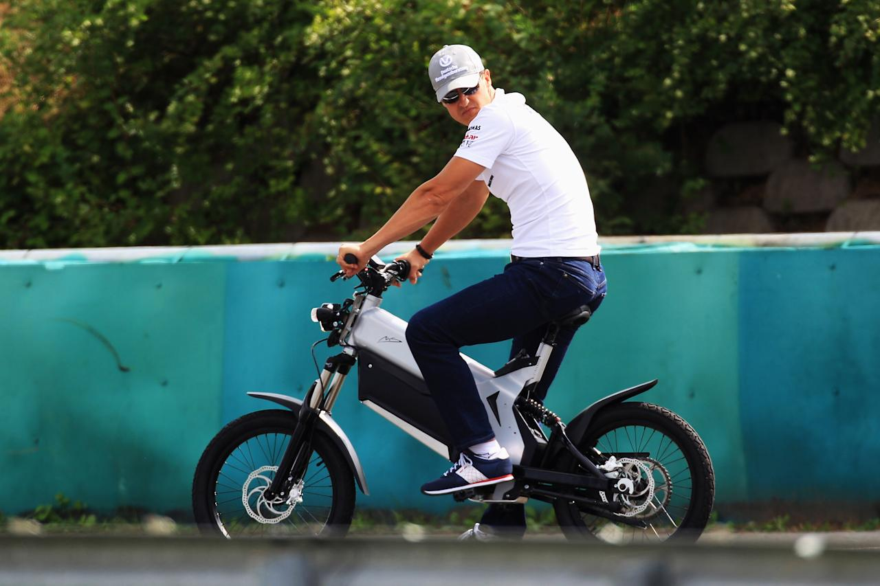 BUDAPEST, HUNGARY - JULY 29:  Michael Schumacher of Germany and Mercedes GP rides around the track on an electric bike during previews to the Hungarian Formula One Grand Prix at the Hungaroring on July 29, 2010 in Budapest, Hungary.  (Photo by Mark Thompson/Getty Images)