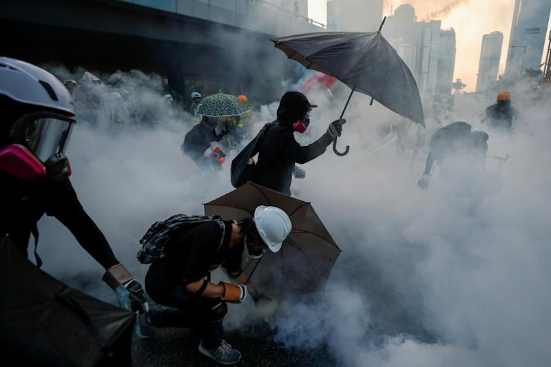 Anti-government protesters protect themselves with umbrellas among tear gas.