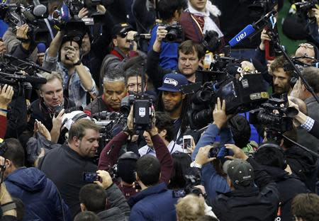 Seattle Seahawks cornerback Richard Sherman is surrounded by cameras as he arrives during Media Day for Super Bowl XLVIII at the Prudential Center in Newark, New Jersey January 28, 2014. REUTERS/Carlo Allegri