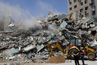 Workers clear the rubble of a building that was destroyed by an Israeli airstrike on Saturday, that housed The Associated Press, broadcaster Al-Jazeera and other media outlets, in Gaza City, Sunday, May 16, 2021. (AP Photo/Adel Hana)