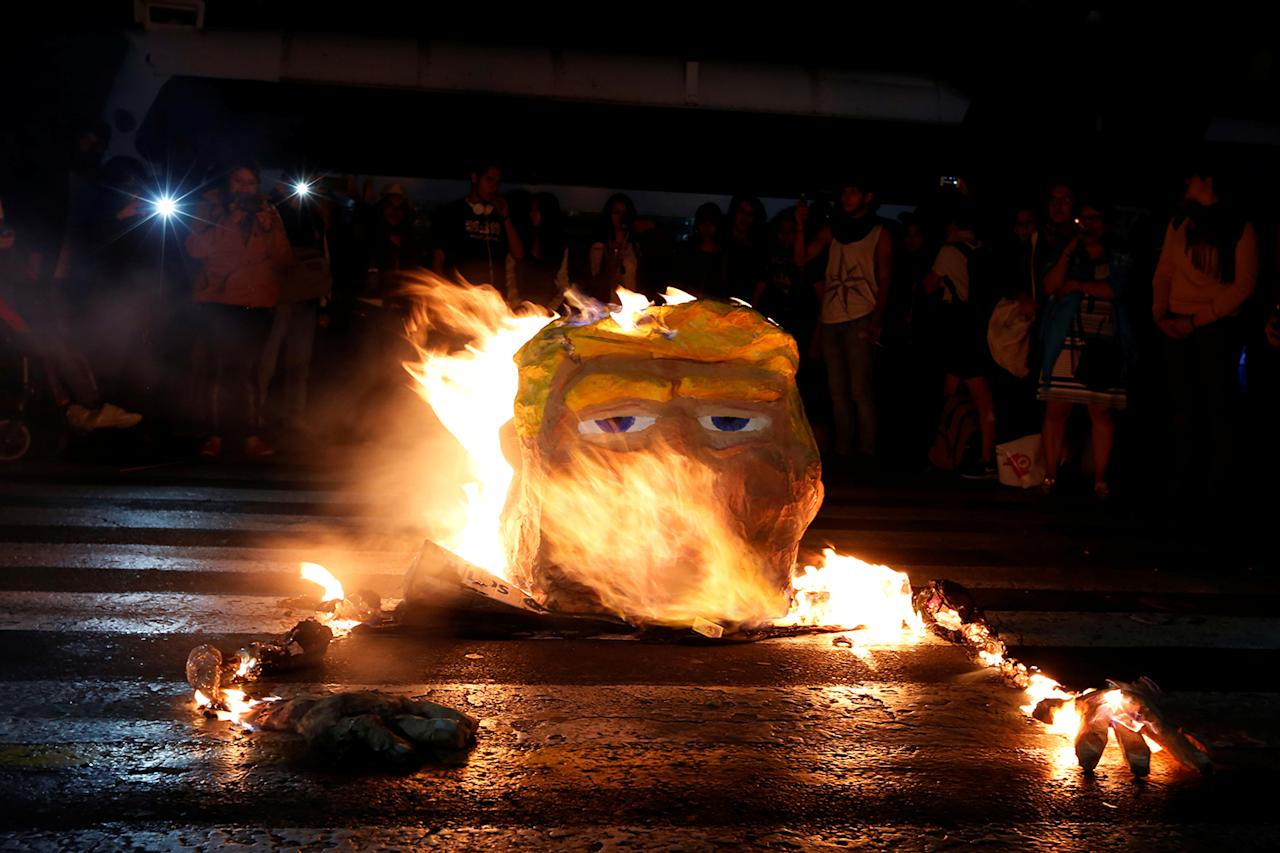 <p>Protesters light a figure of U.S. President Donald Trump on fire during a protest in Mexico City, Mexico January 20, 2017. (REUTERS/Carlos Jasso) </p>