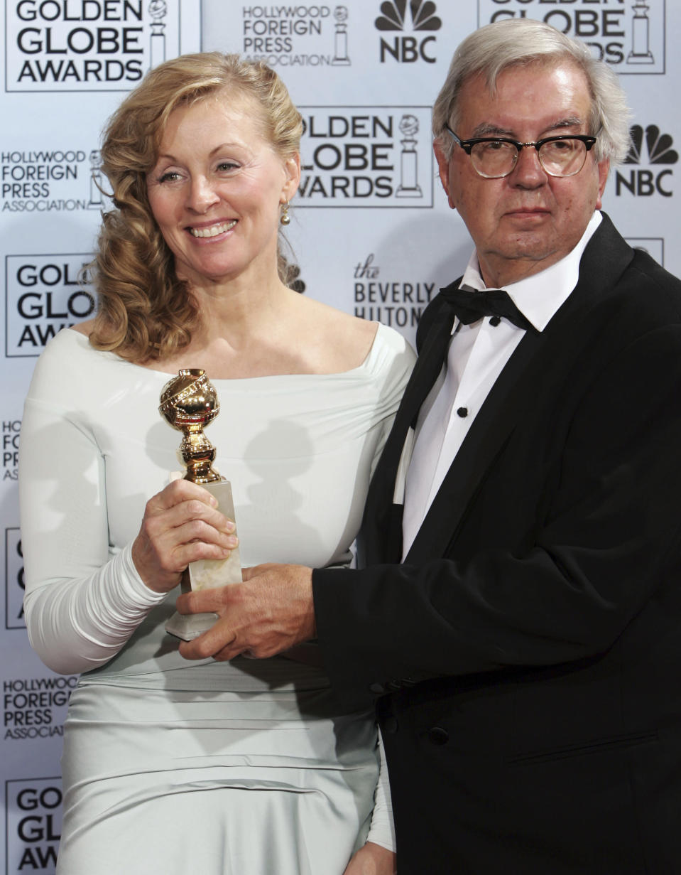 """FILE - Writers Larry McMurtry, right, and Diana Ossana pose with their awards for best screenplay for """"Brokeback Mountain,"""" at the 63rd Annual Golden Globe Awards in Beverly Hills, Calif. on Jan. 16, 2006. McMurtry has died at the age of 84. His death was confirmed Friday, March 26, 2021, by a spokesman for his publisher Liveright. Several of McMurtry's books became feature films, including the Oscar-winning films """"The Last Picture Show"""" and """"Terms of Endearment."""" He also co-wrote the Oscar-winning screenplay for """"Brokeback Mountain."""" (AP Photo/Reed Saxon, File)"""