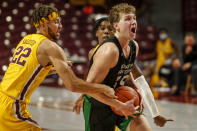 Minnesota guard Gabe Kalscheur (22) fouls North Dakota forward Mitchell Sueker (35) as guard Marcus Carr (5) helps defend in the second half of an NCAA college basketball game Friday, Dec. 4, 2020, in Minneapolis. (AP Photo/Bruce Kluckhohn)