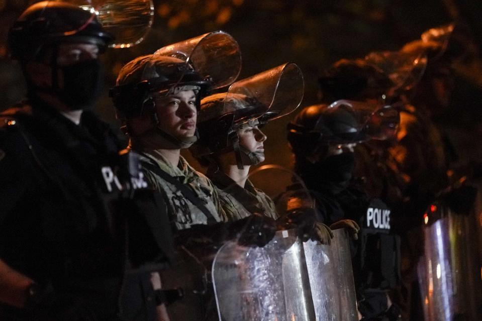 CORRECTS TO JOHN CHISHOLM NOT JOHN CHISOLM - Police and National Guardsmen line up in riot gear Friday, Oct. 9, 2020, in Wauwatosa, Wis. On Wednesday, District Attorney John Chisholm refused to issue charges against Wauwatosa Police Officer Joseph Mensah for the Feb. 2 fatal shooting of 17-year-old Alvin Cole at Mayfair Mall. (AP Photo/Morry Gash)