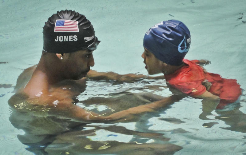 "This May 17, 2013 photo released by Simone Smalls PR shows Olympic gold medalist Cullen Jones give swimming lessons to Niko Diop, a pre-kindergarden student at Harlem's P.S. 125 in New York.  Jones is ambassador for the 5th Annual USA Swimming Foundation's ""Make a Splash Tour,"" providing free swimming lessons, water safety education and awareness at city pools.  (AP Photo/Simone Smalls PR)"