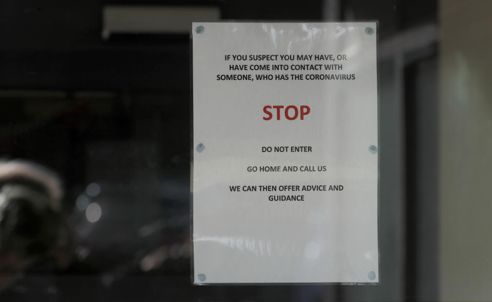 """Signs at the entrance of the County Oak Medical Centre GP practice in Brighton, England, Tuesday, Feb. 11, 2020. The Medical centre has been temporarily closed """"because of an urgent operational health and safety reason"""", following reports a member of staff there was one of those infected with coronavirus, in Brighton, England, Monday, Feb. 10, 2020. Britain has declared the new coronavirus that emerged from China a """"serious and imminent threat to public health'' and announced new measures Monday to combat the spread of the disease.(AP Photo/Frank Augstein)"""