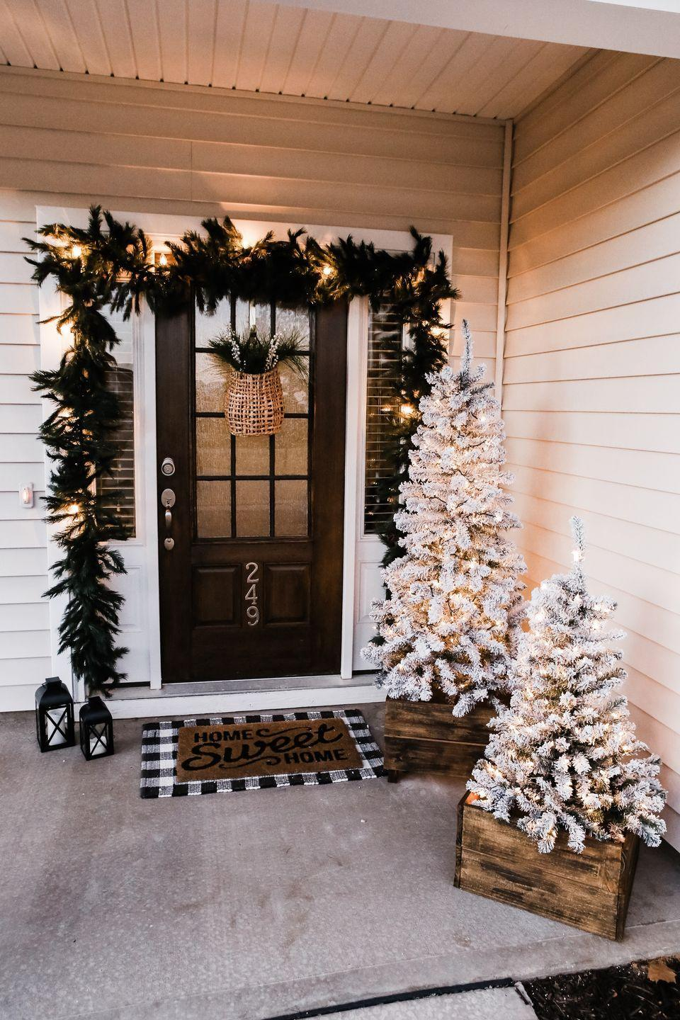 "<p>This neutral holiday tableau by <a href=""https://jordanjean.com/our-festive-home-exterior-for-christmas/"" rel=""nofollow noopener"" target=""_blank"" data-ylk=""slk:Jordan Jean Blog"" class=""link rapid-noclick-resp"">Jordan Jean Blog</a> is both chic and welcoming. She stuck to a black-and-white theme and added earth-toned accents. The hanging wicker basket on the door, filled with fresh greenery, is a stylish touch.</p>"