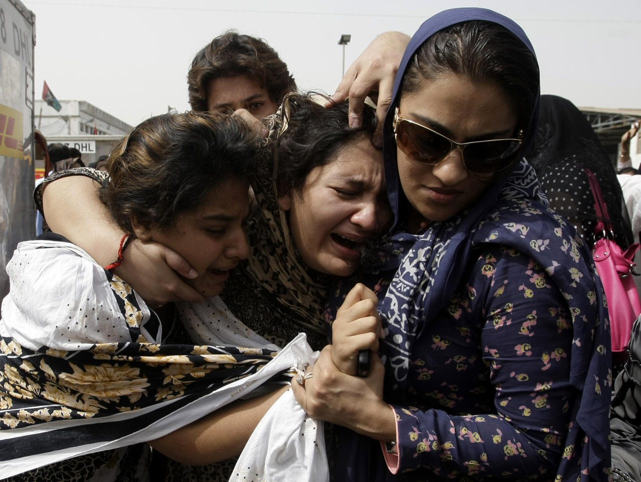 Family members of Pakistani acid attack victim Fakhra Younnus, mourn her death at Karachi airport in Pakistan on Sunday, March 25, 2012. Fakhra, who committed suicide by jumping from the sixth floor of her flat in Rome, was a victim of an acid attack allegedly carried out 12 years ago by her husband, the son of a feudal politician. (AP Photo)