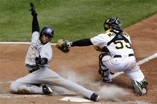Colorado Rockies' Eric Young Jr., left, slides around the tag by Pittsburgh Pirates catcher Michael McKenry in the eighth inning of a baseball game in Pittsburgh, Wednesday, April 25, 2012. Young scored from third on a sacrifice fly to right field by Rockies' Tyler Colvin. The Rockies won the first game of the double header 2-1. (AP Photo/Gene J. Puskar)