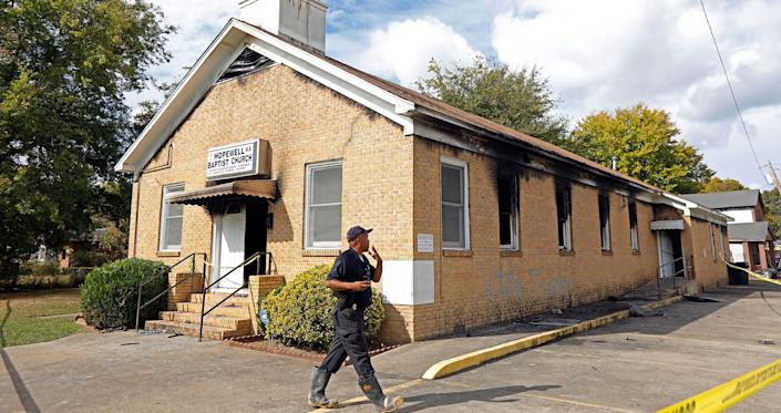 """<p>A state fire marshal investigates the fire damaged Hopewell M.B. Baptist Church in Greenville, Miss., Wednesday, Nov. 2, 2016. """"Vote Trump"""" was spray-painted on an outside wall of the black member church. (AP Photo/Rogelio V. Solis) </p>"""