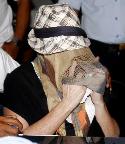 Australian Schapelle Corby, covering her face, gestures at the correctional office after she received her parole in Bali, Indonesia, Monday, Feb. 10, 2014. The Australian woman convicted of smuggling marijuana into Indonesia in 2005 has been released from jail on parole. She was convicted of smuggling 4.2 kilograms (9 pounds) of marijuana onto Bali and sentenced to 20 years in prison. (AP Photo/Firdia Lisnawati)