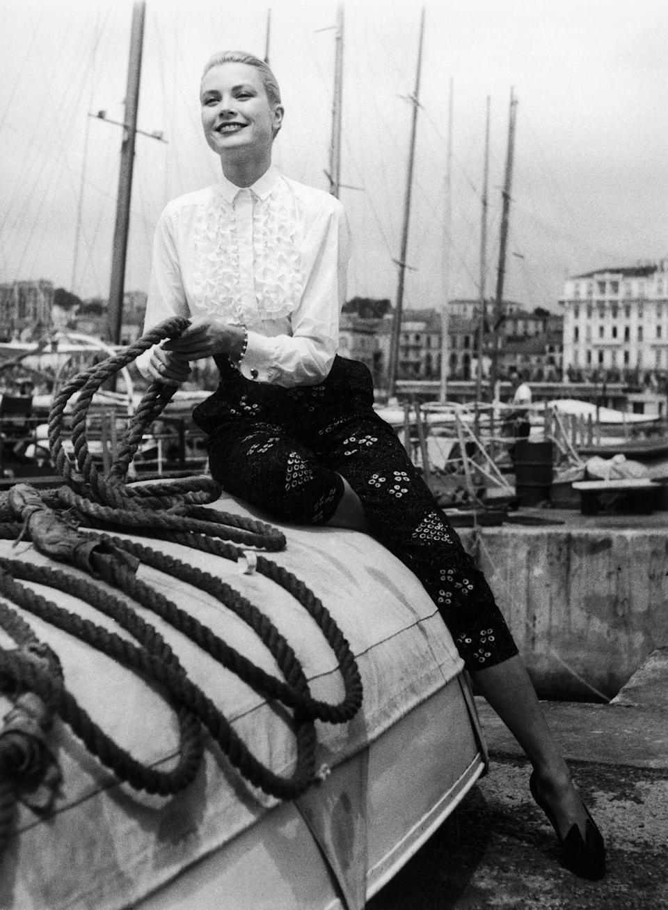 <p>Kelly explores the docks in France as she arrives in Cannes for the annual film festival. The actress looks polished in a ruffled button-down shirt and black printed cigarette pants. </p>