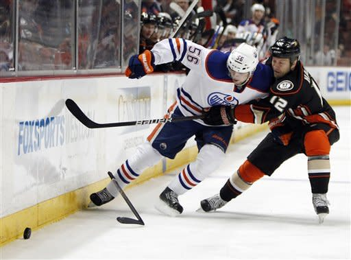 Edmonton Oilers center Teemu Hartikainen (56) battles Anaheim Ducks left wing Niklas Hagman in the first period of an NHL hockey game in Anaheim, Calif., Sunday, April 1, 2012. (AP Photo/Christine Cotter)