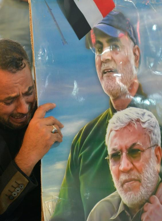 An Iraqi man in the Shiite holy city Najaf holding a portrait of slain commander Abu Mahdi al-Muhandis and Iranian Revolutionary Guard commander Qasem Soleimani a year after they died in a US strike