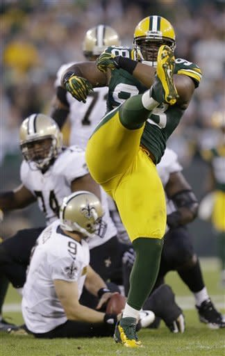 Green Bay Packers' C.J. Wilson, front, celebrates a sack of New Orleans Saints' Drew Brees during the second half of an NFL football game Sunday, Sept. 30, 2012, in Green Bay, Wis. Green Bay won 28-27. (AP Photo/Jeffrey Phelps)