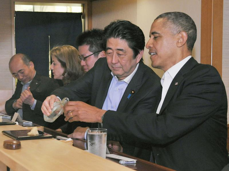 Japanese Prime Minister Shizo Abe fills U.S. President Barak Obama's glass during dinner at Sukiyabashi Jiro sushi restaurant in Tokyo on April 23, 2014.