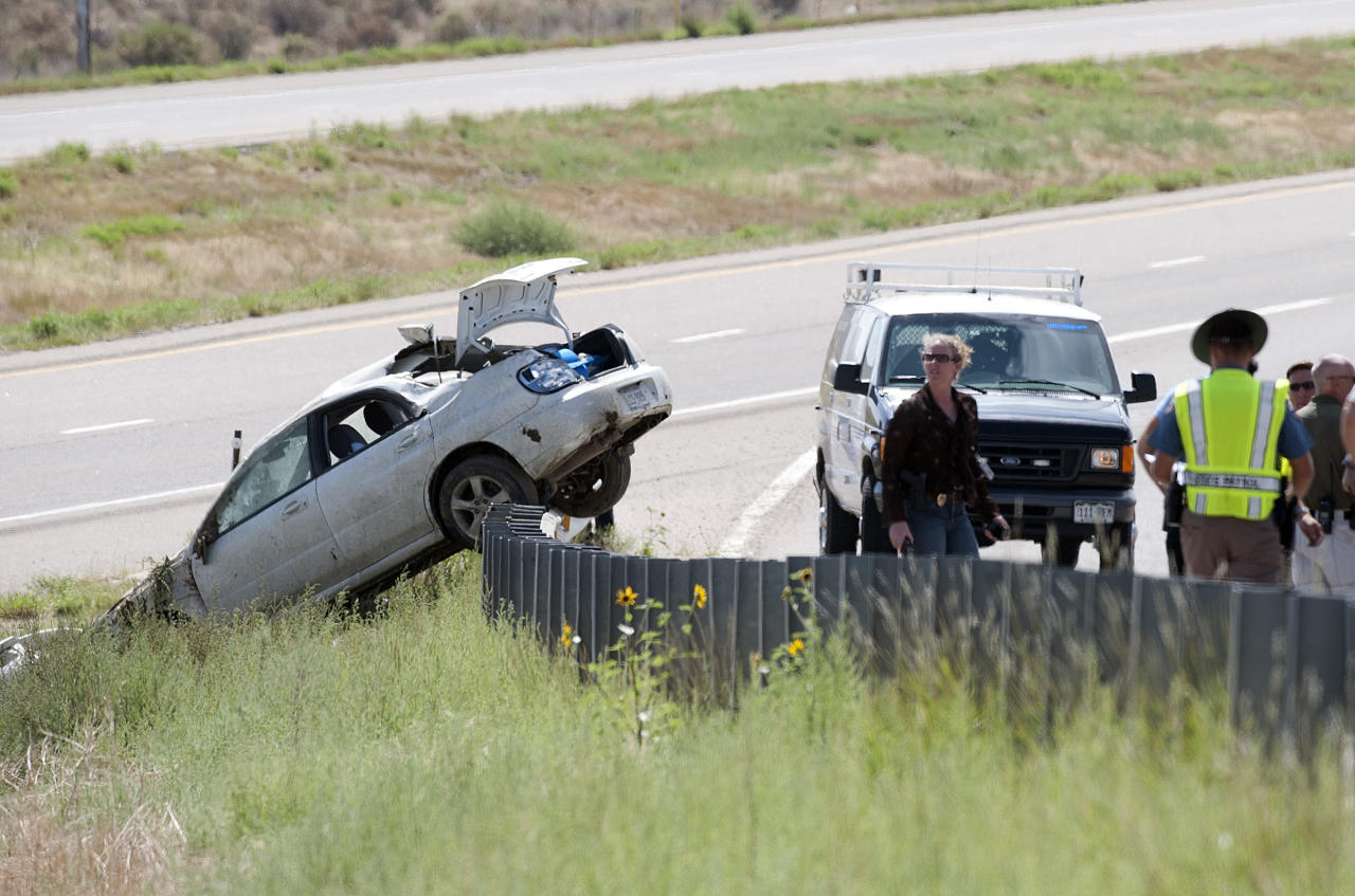 Police are pictured at the scene where three fugitive siblings wanted in Florida and Georgia crashed their automobile, left, and were arrested near Walsenburg, Colo., on Wednesday, Aug. 10, 2011. The trio, Ryan Edward Dougherty, 21; Dylan Dougherty Stanley, 26; and Lee Grace Dougherty, 29, had been targets of a nationwide search after alleged crimes last week in which they were accused of shooting at a police car during a chase and robbing a bank with assault weapons. FBI Special Agent Steve Emmett confirmed that the three were in custody in Colorado. (AP Photo/Pueblo Chieftain, Mike Sweeney)