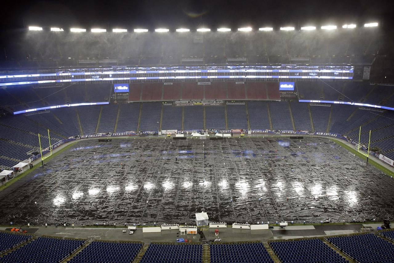 Rain falls on the tarp-covered field before an AFC divisional NFL playoff football game between the Indianapolis Colts and New England Patriots in Foxborough, Mass., Saturday, Jan. 11, 2014. (AP Photo/Matt Slocum)